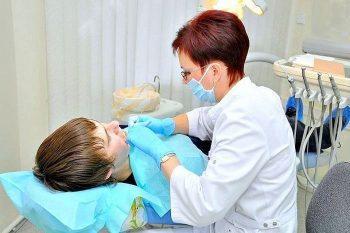 Врач лечит зубы