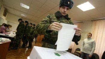Военнослужащий опускает бюллетень на выборах